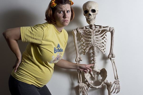 Woman with lower back pain posing with Skeleton
